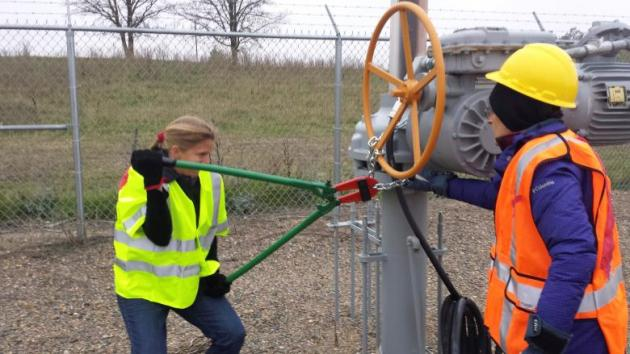 Activists are seen attempting to cut chains after trespassing into a valve station for pipelines carrying crude from Canadian oils sands into the U.S. markets near Clearbrook